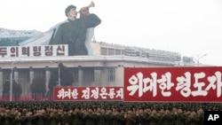 """Tentara Korut memberikan sambutan yang meriah dengan bertepuk tangan dekat spanduk bertuliskan """"Semangat Revolusioner"""", """"Komandan yang Luar Biasa, Kim Jong Un"""" dan """"Pemimpin yang Luar Biasa"""" dalam pawai massal di Lapangan Kim Il Sung Square di Pyongyang, Korea Utara (14/12)."""