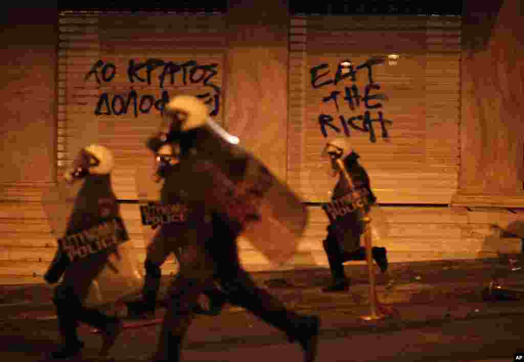 Riot police chase protesters in front of a hotel during a protest in Athens after a Greek retiree shot himself, April 4, 2012. (AP)