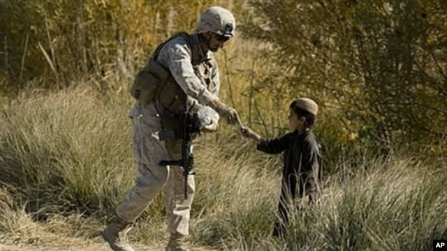 U.S. Marine 1st Sergeant Christopher Adams of 2nd Battalion 2 Marines of 2nd Marine Expeditionary Brigade gives an Afghan child a pen in Mian Poshteh in Helmand Province. 26 Nov 2009