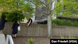 Students wearing graduation clothing pose for photos at Carnegie Mellon University.