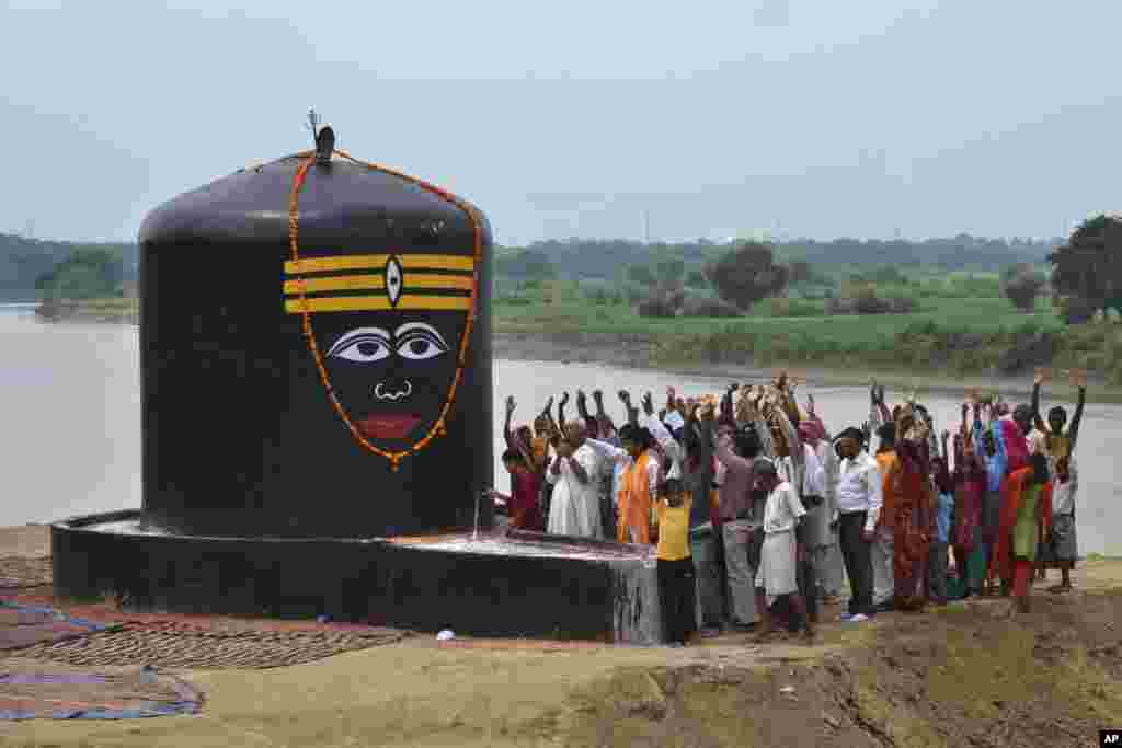 Devotees raise their hands and chant religious slogans as they worship newly installed 'lingam', representing Hindu deity Shiva on the banks of the river Yamuna in Agra, India.