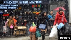 People carrying luggages leave a railway station in snow in Wuhan, Hubei province, Jan. 31, 2016.