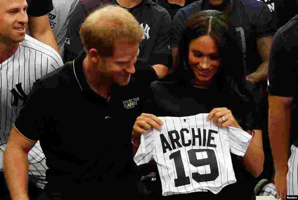 Britain's Prince Harry and Meghan, Duchess of Sussex, receive a present for baby Archie as they meet players of the New York Yankees before a match against the Boston Red Sox in London, June 29, 2019.