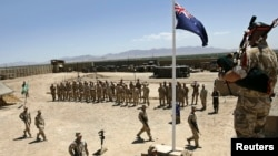FILE - Australian and British troops stand at attention during an ANZAC day ceremony at Camp Armadillo, in Helmand Province.