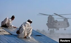 Afghan workers build a combat resupply area while a Chinook CH-47F transport helicopter prepares to land at FOB Salerno, Afghanistan on December 2, 2009.