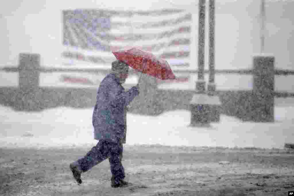 A pedestrian passes in front of an American flag as snow falls in Manchester, New Hampshire. Stoic New Englanders doggedly went about their business as a winter storm, that could drop close to a foot of snow in some areas, struck the region ahead of the state's presidential primary vote next week.