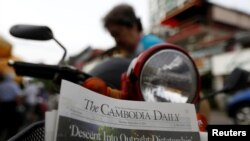FILE - A woman buys the final issue of The Cambodia Daily newspaper at a store on a street in Phnom Penh, Cambodia, Sept. 4, 2017.