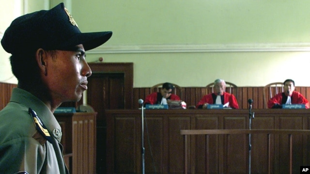 A Cambodian police officer guards the Appeals Court in Phnom Penh, Cambodia, as the judges read their verdict in front of an empty dock, file photo.