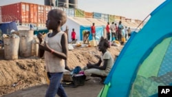 FILE - A young displaced girl washes clothes alongside a row of tents in the United Nations camp in Juba, South Sudan, Feb. 12, 2014.