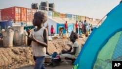 A young girl washes clothes alongside a row of tents in the United Nations camp in Juba, South Sudan, Feb. 12, 2014.