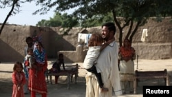 Muhammad Ikram (32 tahun) yang lahir tanpa lengan dan jago bermain biliar dengan menggunakan dagunya bermain bersama adiknya di rumahnya di Samundri, Pakistan, 20 Oktober 2020. (Foto: Reuters)