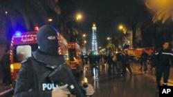 Un policía en Túnez bloquea el ingreso de la prensa al lugar donde una explosión en un autobús que llevaba miembros de la guardia presidencial dejó al menos 12 muertos. Nov. 24 de 2015.