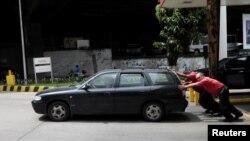 Empleados de una gasolinera empujan un auto en Caracas.