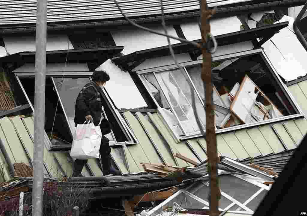 A local resident leaves after picking up her belongings from her collapsed house after a 6.2 magnitude earthquake hit the area the night before, in Hakuba, some 300 kms northwest of Tokyo, Nagano prefecture.
