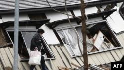 Un résident de Hakubadans la préfecture de Nagano, marche devant les débris d'un bâtiment, 23 novembre 2014.