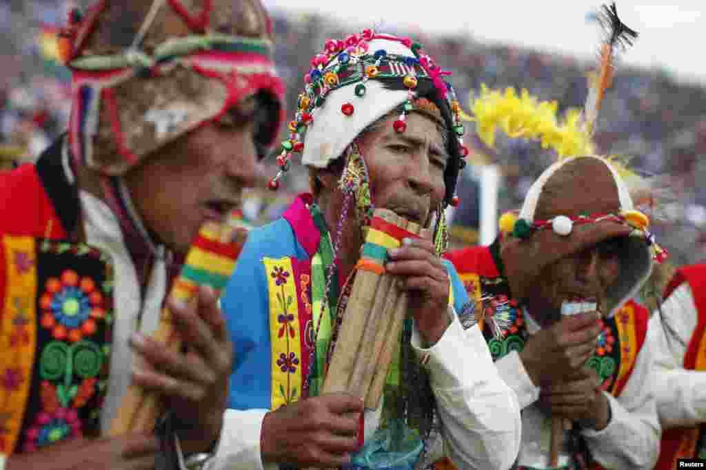 Indigenous men blow traditional flutes in Santa Cruz de la Sierra, Bolivia, June 14, 2014.