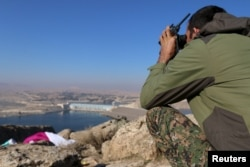 FILE - A fighter from the Democratic Forces of Syria takes an overwatch position at the top of Mount Annan overlooking the Tishrin dam, after they captured it from Islamic State militants, south of Kobani, Dec. 27, 2015.