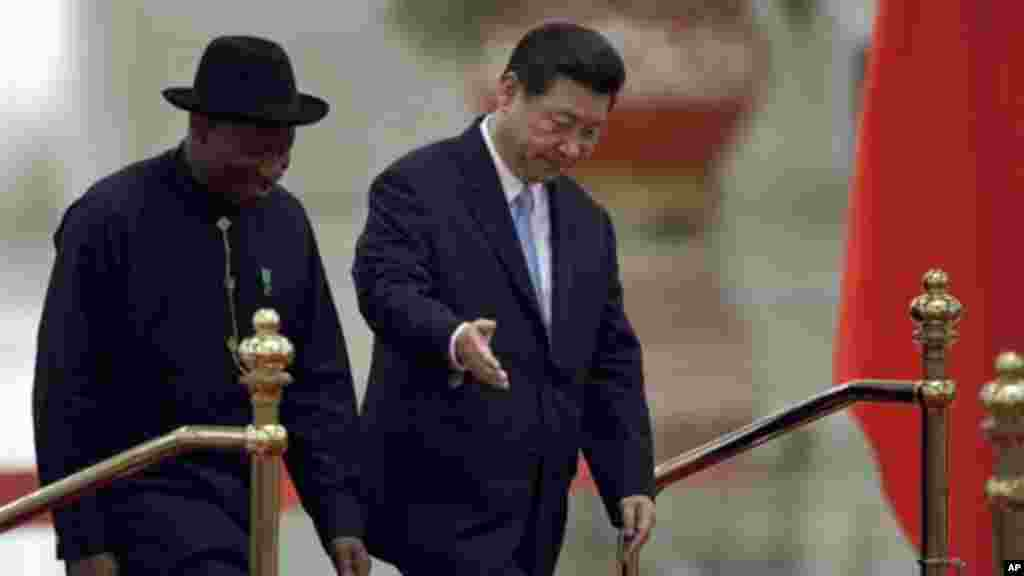 Chinese President Xi Jinping gestures to President Jonathan as they walk together during a welcome ceremony at the Great Hall of the People in Beijing, China.