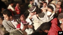 也門反政府示威者在星期日和警方的衝突中抬著受傷者
