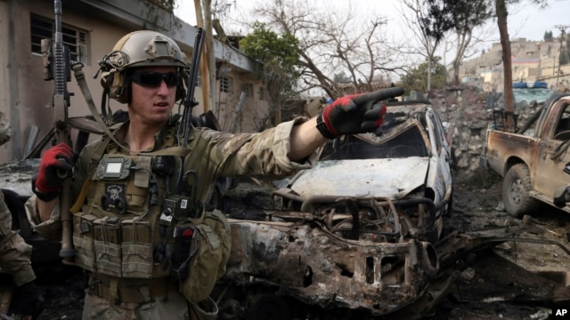 FILE - A U.S. soldier is seen at the site of a suicide bombing at a police compound in the Surobi district of Kabul, Feb. 21, 2014.