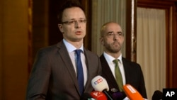 Hungarian Foreign Minister Peter Szijjarto, with government spokesman Zoltan Kovacs at right, talks to reporters in Budapest about plans to build a fence along the Hungarian-Serbian border to try to stop migrants from entering, June 17, 2015.