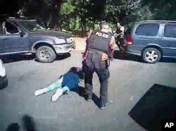 This image made from video provided by the Charlotte-Mecklenburg Police Department, Sept. 24, 2016, shows Keith Scott on the ground as police approach him in Charlotte, N.C., on Sept. 20, 2016.