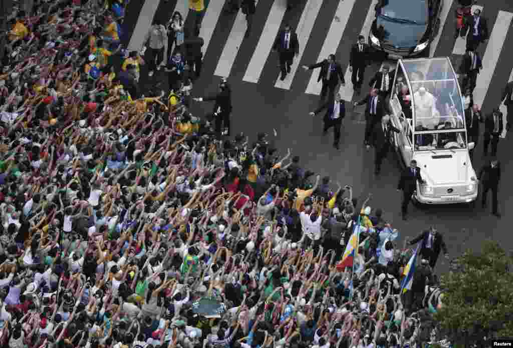 Pope Francis greets the crowd of faithful from his popemobile in downtown Rio de Janeiro, Brazil, July 22, 2013.