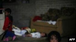 Một đứa trẻ ngồi ở nhà trong 1 khu phố nghèo ở thành phố Mexico, 29/7/2011