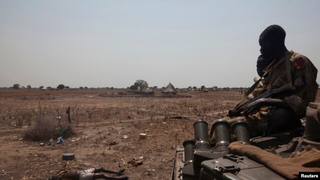 An SPLA tank drives past the remains of a rebel soldier killed near Bor on January 26, 2014, days after a peace deal was signed. South Sudan opposition forces accused the government of fresh attacks at the weekend, including on the hometown in Unity state of former vice president Riek Machar. REUTERS/George Philipas