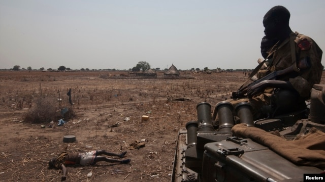 An SPLA military tank drives past the remains of a rebel soldier killed in the frontline at Mathiang near Bor, South Sudan, January 26, 2014.