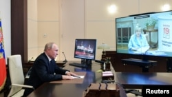 Russian President Vladimir Putin attends a meeting with head of the Central Election Commission Ella Pamfilova, via a video conference call at the Novo-Ogaryovo state residence outside Moscow, Sept. 20, 2021. (Sputnik/Alexei Druzhinin/Kremlin via Reuters)