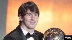 Bintang sepakbola Argentina Lionel Messi memegang Piala Bola Emas FIFA dalam acara di Zurich, Swiss, hari Senin (10/1).