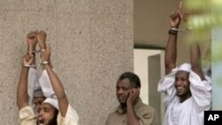 Three of four Islamists (excluding man in center) accused in 2008 killing of US diplomat and his Sudanese driver, raise their hands and shout slogans as they walk out of a Sudanese court in Khartoum (24 Jun 2009 file photo)
