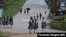 Wearing masks to curb the spread of the new coronavirus, students walk to the one open school in Campohermoso, Colombia, Thursday, March 18, 2021. (AP Photo/Fernando Vergara)