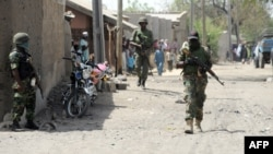 FILE - Nigerian soldiers are seen patrolling Baga, a town in the northeastern state of Borno, April 30, 2013.