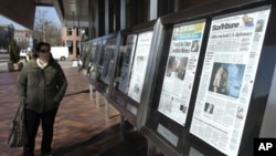 A woman reads the front pages of U.S. newspapers outside the Newseum in Washington.
