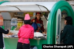A vendor sells food and drinks out of a kiosk in Pyongyang, North Korea.