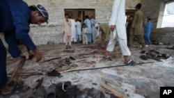 Pakistani villagers clean the floor of a mosque targeted by a suicide attacker in the Pakistani tribal area of Khyber, Aug. 19, 2011.