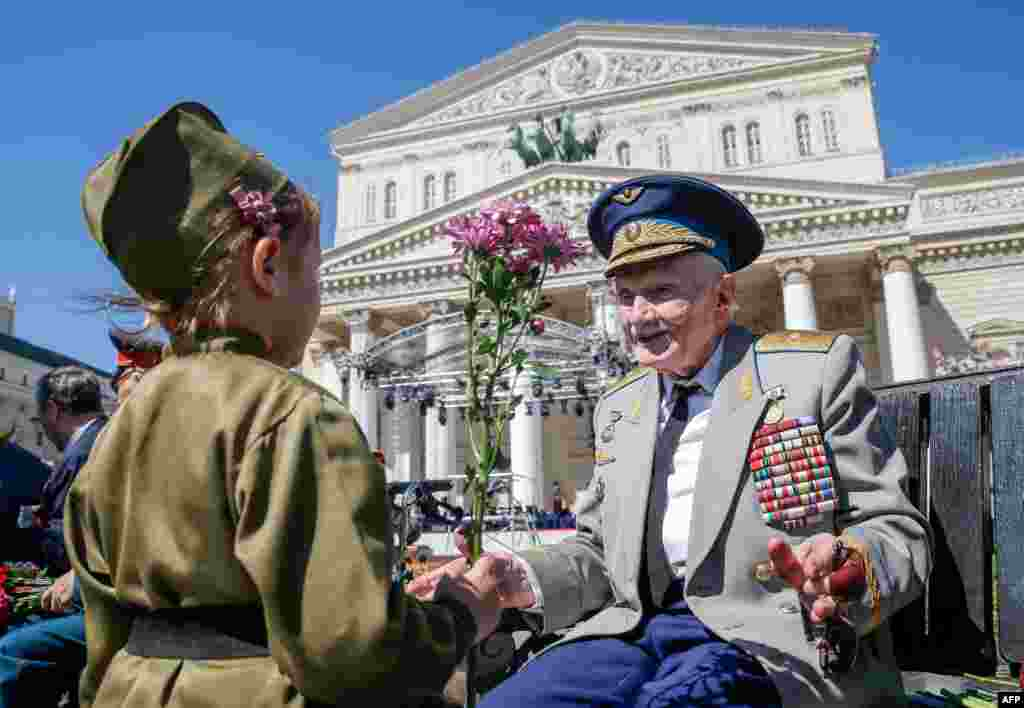 A child presents a flower to a World War II veteran in front of the Bolshoi Theater during Victory Day celebrations in downtown Moscow, Russia.