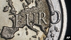 The map of Europe is featured on the face of a two Euro coin seen in this photo illustration.