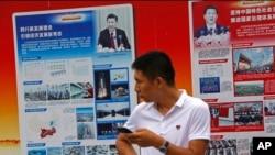 2018年8月22日,北京地铁站外的政府宣传广告牌宣传中国国家主席习近平和中国的经济成就,一名男子站在旁边。