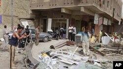 ຝູງຊົນພາກັນຫູ້ມເບິ່ງ ບ່ອນລົດຖືກວາງລະເບີດແຕກ ຢູ່ຄູ້ມ Amil ໃນກູງ Baghdad, Iraq, ທີ່ 19, ເມສາ 2012.