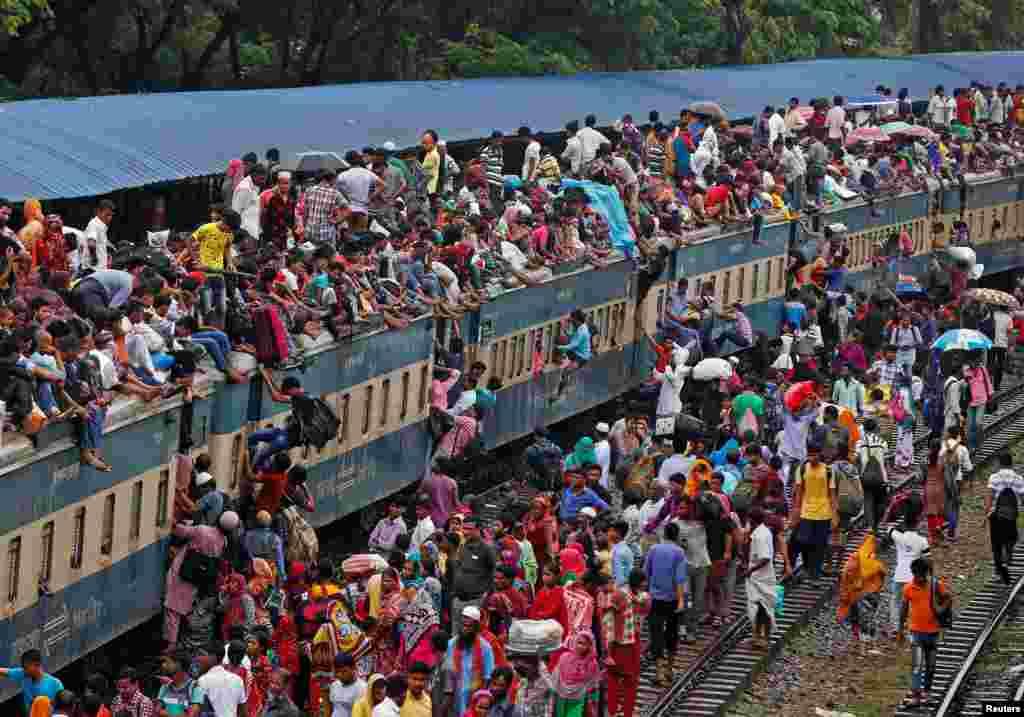 Warga Bangladesh memenuhi kereta hingga ke atapnya, untuk mudik ke kampung halaman pada akhir bulan Ramadan, di stasiun di ibukota Dhaka.