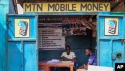 In this photo taken Tuesday, Sept. 10, 2019, a man sits in his mobile money kiosk which specializes in sending money from South Sudan to Uganda, in the capital Juba, South Sudan