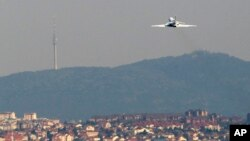 FILE - A Serbian government Falcon plane is seen flying over Belgrade, Serbia.