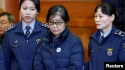 ນາງ Choi Soon-sil, ແມ່ຍິງທີ່ເປັນສູນກາງ ຂອງຄະດີການເມືອງ ເກົາຫຼີໃຕ້ ຜູ້ຊຶ່ງເປັນໝູ່ ກັບອະດີດປະທານາທິບໍດີ Park Geun-hye, ກຳລັງຍ່າງເຂົ້າໄປຟັງ ຄຳຖະແຫຼງຂອງສານ ໃນການດຳເນີນຄະດີ ປ. Park Geun-hye ທີ່ສານ ລັດຖະທຳມະນູນ ໃນນະຄອນໂຊລ, ເກົາຫຼີໃຕ້, 16 ມັງກອນ 2017.