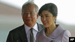 Visiting Thailand's Prime Minister Yingluck Shinawatra and her Malaysian counterpart Najib Razak walk to step down from the stage after the welcoming ceremony outside Razak's office in Putrajaya near Kuala Lumpur, February 20, 2012.