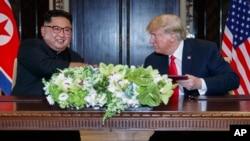 ປະທານາທິບໍດີ ສະຫະລັດ ທ່ານ ດໍໂນລ ທຣຳ ແນມເບິ່ງຜູ້ນຳ ເກົາຫຼີເໜືອ ທ່ານ ກິມ ຈົງ ອຶນ ຫຼັງຈາກການລົງນາມ ໃນເອກະສານຂອງພວກທ່ານ ທີ່ບ້ານພັກຕາກອາກາດ ກາແປລລາ, ເກາະ ເຊັນໂຕຊາ, ປະເທດ ສິງກະໂປ. 12 ມິຖຸນາ, 2018. (AP Photo/Evan Vucci)