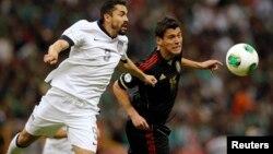 Hérculez Gómez, de Estados Unidos, y Hector Moreno de México, se disputan el balón en un partido que terminó sin goles.