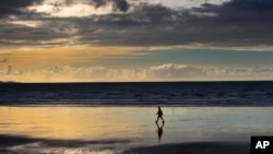 A person walks on Orewa Beach in Auckland, New Zealand, on June 5, 2021. New Zealand has recorded its warmest June since recordkeeping began, as ski fields struggle to open and experts predict shorter southern winters in the future. (Brett Phibbs/New Zealand Herald via AP)